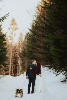 Para młoda z sankami w śniegu